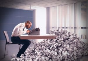 struggling writer with a mountain of paper wads