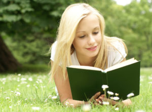 pretty girl reading in a field